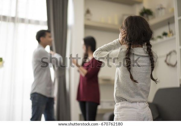 In back view, Little girl puts her hands on her ears because she does not want to hear her dad and mom quarrel. close ears, Family Dramatic scene, Parrents issues, Social and parrents problem concept