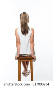 back view of little girl sitting on high chair