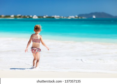 Back view of a little girl at tropical beach