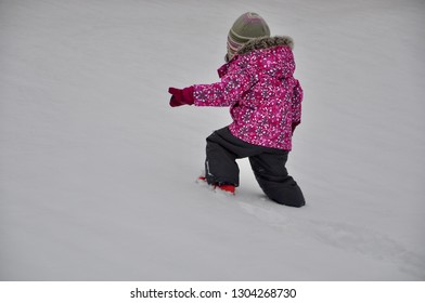 Back view of a little girl walking in snowy grounds