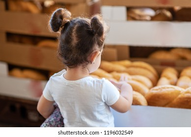 Back view little girl, while choosing fresh bread loaf in bakery department. Portrait of happy young toddler shopping for groceries in supermarket. Kid on Fresh challah bread for shabbat background.