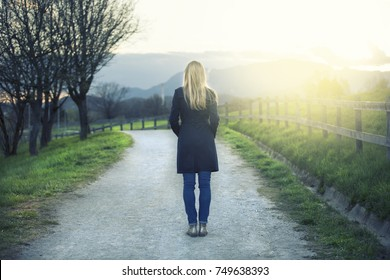 Back view of lonely blonde woman standing on the sunny path in the park.
