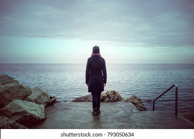 Back View Of Lonely Woman Looking The See Loneliness Concept In Winter Season
