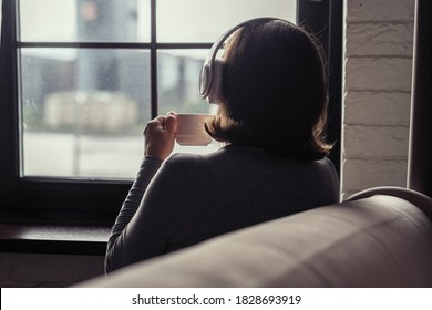 Back view of lonely сaucasian young woman enjoying having breakfast with cup of coffee and listenning music in headphones sitting near window at cold winter morning.