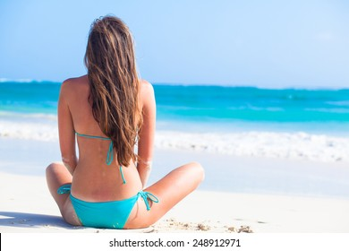 back view of long haired girl in bikini and straw hat on tropical caribbean beach
