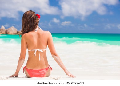 back view of long haired woman in bikini on tropical beach