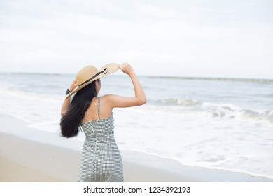 back view of long haired young asian woman in straw hat on tropical beach
