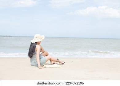 back view of long haired young woman in straw hat on tropical beach