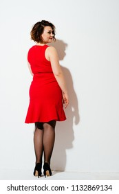 Back view of lovely plus size lady in red dress and high-heels looking over shoulder while standing on white background