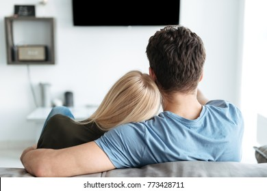 Back view of lovers hugging and sitting on sofa and watching TV in living room