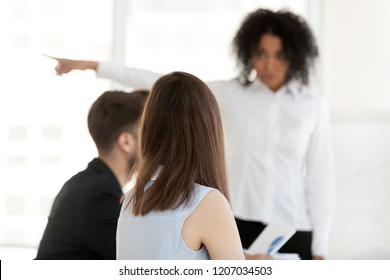 Back view of mad African American businesswoman point at doors asking employees leave meeting, angry black female boss annoyed with workers misconduct or misbehavior request quit briefing