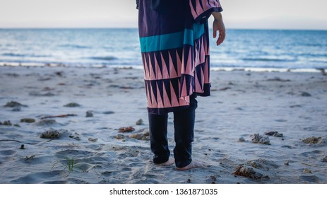 Back view of Malaysian traditional baju kurung lonely woman in sandy beach.