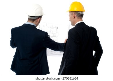 Back view of male architects discussing project plan