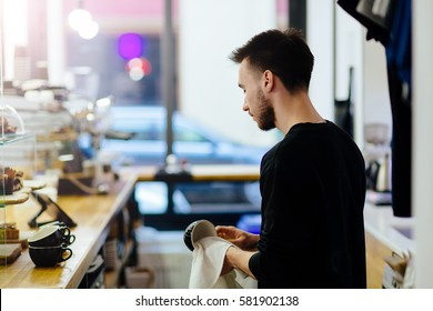 Back view of male cafe worker wipes a dishes.