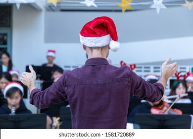 Back view of a male conductor, wearing casual outfit with red santa hat, conducting his young band performing Christmas music at an outdoor event, holiday spirit concept