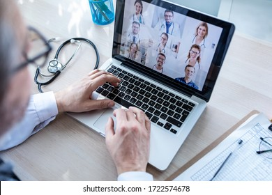 Back view of male doctor having video conference on laptop with his colleagues at home.