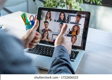 Back view of male employee making a gesturing approval with thumb fingers while speak on video call with diverse colleagues on online briefing with laptop at home.
