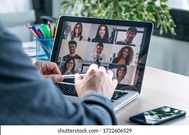 Vista posterior de un empleado masculino hablando en videollamadas con diversos colegas en una reunión informativa en línea con un portátil en casa.