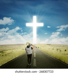 Back view of male musician carrying a guitar and walk on the road to the cross