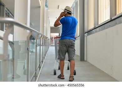 Back view of male person walking talking on mobile smart phone during shopping. Cart on store background.
