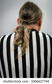 Back view of a male referee with ponytail hair in black and white striped dress.