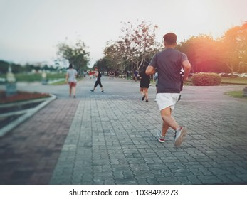 Back view of male runner running on the road with blurred people traveler walking in the park .