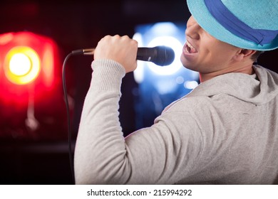 back view of male singer wearing blue hat. handsome man singing into microphone alone