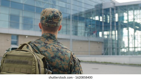 Back view of male soldier leaving on military service. Man in military uniform putting bag on shoulder and walking to airport terminal. Concept of military service, army, duty