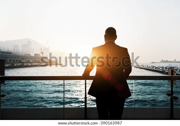 Back view of male successful entrepreneur enjoying evening sunset while standing outdoors in marina port. Silhouette of male skilled and confident businessman is thinking about his future plans