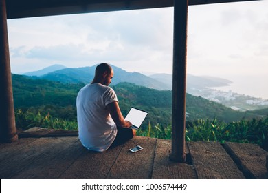 Back view of male traveler blogger work remote on netbook computer while enjoying amazon nature landscape view outdoors. Young man using online banking for sending money everywhere you are from laptop