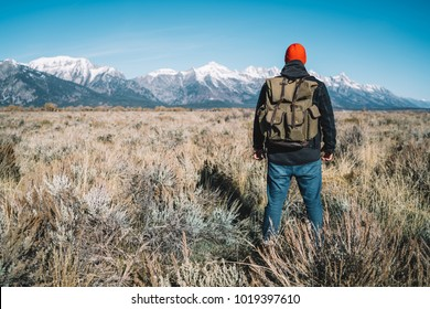 Back view of male traveler looking at mountain peaks standing on field ready to reach tops, hipster guy with backpack discovering beautiful nature of USA at hiking wander journey in wild environment