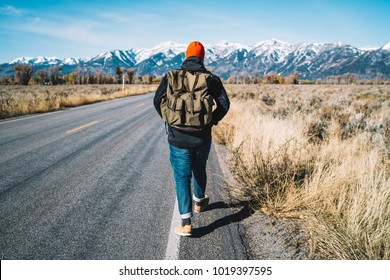 Back view of male traveler walking on asphalt road going to explore wild environment at winter, hipster guy with rucksack getting to mountain hills with snowy peaks by foot during hitch-hiking trip