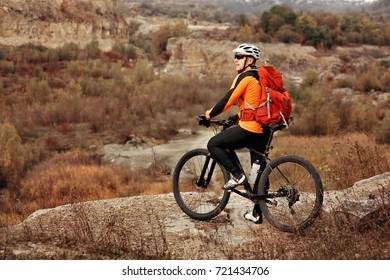back view of a man with a bicycle and red backpack against the blue sky. cyclist rides a bicycle.