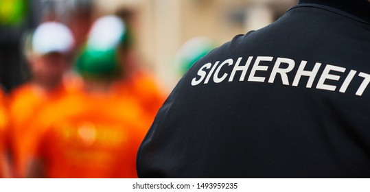 """Back view of a man with a black waistcoat with the German inscription """"Sicherheit"""" (Translation: security)"""