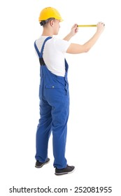 back view of man builder in blue uniform holding measure tape isolated on white background