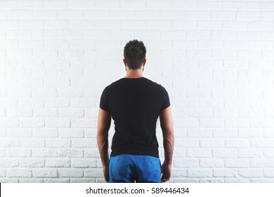 Back view of man in casual black shirt with no print and jeans on white brick wall background. Mock up, Retail concept