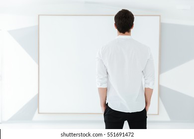 Back view of man dressed in white shirt standing near big board.