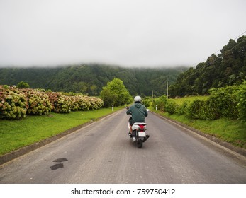 Back view of man driving a motorbike in San Miguel island, Azores. Endless road ahead of him