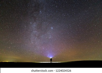 Back view of man with head flashlight standing on green grassy field under beautiful dark blue summer starry sky. Night photography, beauty of nature concept. Wide panorama, copy space background.