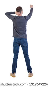 Back view of a man in jeans points his hand upwards. Rear view people collection.  backside view of person.  Isolated over white. The man in surprise pulls his head and points his finger forward.