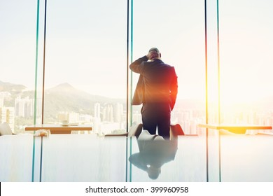Back view of a man lawyer dressed in suit is resting after his a failed court hearing, while is standing in modern coffee shop interior against window with copy space background for your text message