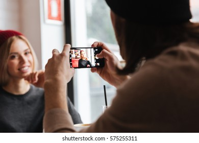 Back view of Man making photo on smartphone of woman sitting by the table in cafe