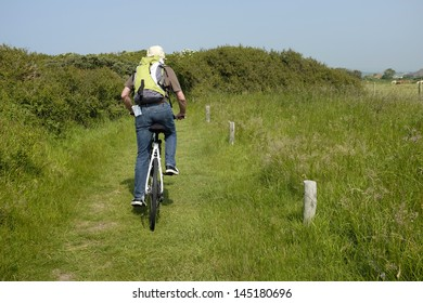 back view of man on a bicycle in nature