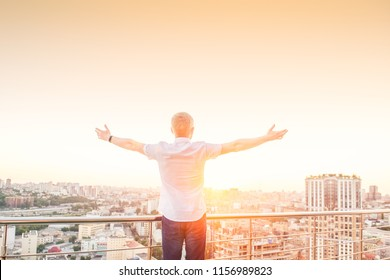 Back view Man on a high rise building balcony overlooking city with hands rised up to sky, feeling and celebrating freedom, victory, sucsess. Expressing his joy of life. Positive emotions. Copy space.