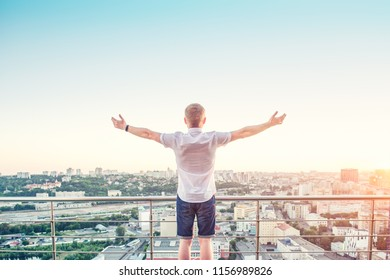 Back view Man on a high rise building balcony overlooking city with hands rised up to sky, feeling and celebrating freedom, victory, sucsess. Expressing his joy of life. Positive emotions. Copy space