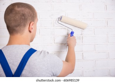 back view of man painter in workwear painting white brick wall with paint roller