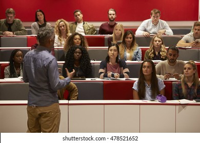 Back view of man presenting to students at a lecture theatre