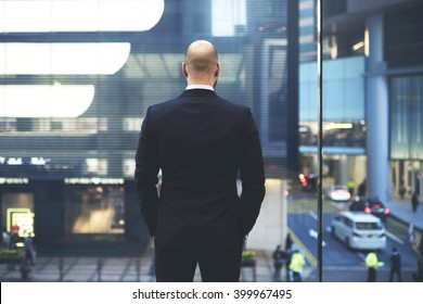 Back view of man proud CEO in luxury suit is watching at big office window at central street of New York, while is resting after important meeting with international partners during business trip