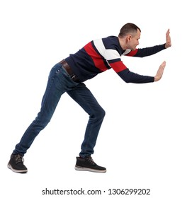 back view of man pushes wall. Isolated over white background. Rear view people collection. backside view of person. The guy in the sweater pushes something in front of him.