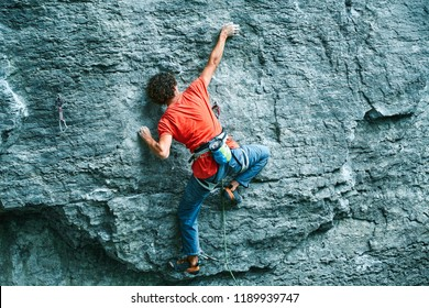 back view of man rock climber in bright blue pants climbing on the cliff. rock climber climbs on a rocky wall. man making hard move on the challenging route